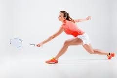Jovem mulher que joga o badminton sobre o fundo branco fotos de stock royalty free