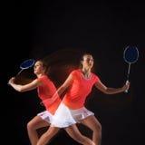 Jovem mulher que joga o badminton sobre o fundo preto Fotos de Stock