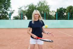 Jovem mulher que joga o tênis que guarda uma raquete Menina loura que levanta no campo de tênis no vestido azul do esporte foto de stock