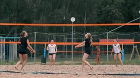 Jovem mulher que joga o voleibol na praia em uma equipe que realiza um ataque que bate a bola Menina em batidas do movimento lent video estoque
