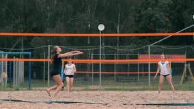 Jovem mulher que joga o voleibol na praia em uma equipe que realiza um ataque que bate a bola Menina em batidas do movimento lent filme