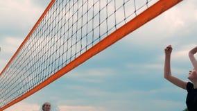 Jovem mulher que joga o voleibol na praia em uma equipe que realiza um ataque que bate a bola Menina em batidas do movimento lent vídeos de arquivo