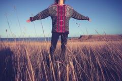 Jovem mulher que joga seus braços para trás no prado pelo mar Imagens de Stock Royalty Free