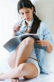 Jovem mulher que lê um compartimento que senta-se no assoalho Imagens de Stock Royalty Free
