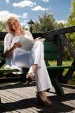 Jovem mulher que lê um livro Fotos de Stock Royalty Free