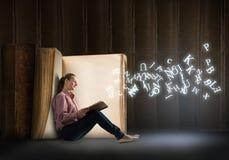 Jovem mulher que lê um livro Imagem de Stock