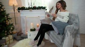 A jovem mulher que lê um livro, ao sentar-se no sofá, feriados do Natal em uma atmosfera acolhedor, relaxa pela chaminé video estoque