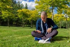 Jovem mulher que lê um livro em linhas de uma leitura do parque da mão Fotografia de Stock Royalty Free