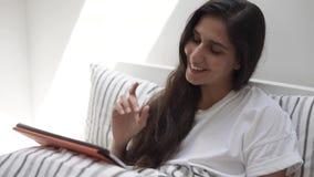 Jovem mulher que lê um livro em uma tabuleta e em um sorriso portáteis modernos filme