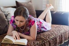 Jovem mulher que lê um livro que encontra-se no sofá imagem de stock royalty free