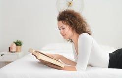 Jovem mulher que lê um livro na cama na manhã foto de stock royalty free
