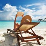 Jovem mulher que lê um livro na praia Imagem de Stock Royalty Free