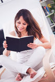 Jovem mulher que lê um livro na sala Foto de Stock
