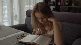 Jovem mulher que lê um livro que senta-se na tabela no sofá acolhedor no café filme