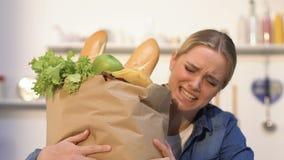 A jovem mulher que leva o saco de papel pesado com os produtos da loja, precisa a entrega filme