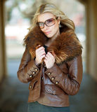 Jovem mulher que levanta óculos de sol fora vestindo imagem de stock