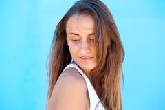 Jovem mulher que levanta contra o fundo azul Fotografia de Stock