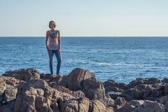 Jovem mulher que levanta em rochas pelo Mar Negro Fotos de Stock Royalty Free