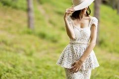Jovem mulher que levanta em um vestido branco com um chapéu Imagens de Stock