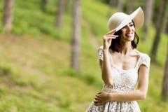 Jovem mulher que levanta em um vestido branco com um chapéu Fotos de Stock