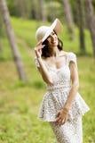 Jovem mulher que levanta em um vestido branco com um chapéu Imagens de Stock Royalty Free