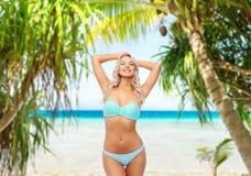 Jovem mulher que levanta no biquini na praia imagem de stock