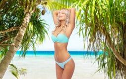 Jovem mulher que levanta no biquini na praia imagem de stock royalty free