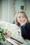 Jovem mulher que levanta perto do piano branco com o atril de madeira cinzelado imagens de stock