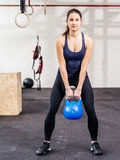 Jovem mulher que levanta um kettlebell Imagem de Stock