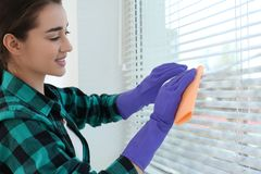 Jovem mulher que limpa cortinas de janela com o pano Antes e depois da limpeza foto de stock