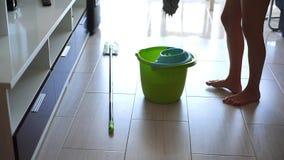 Jovem mulher que limpa o assoalho de telha branco com o espanador em casa video estoque
