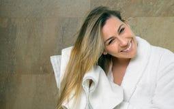 Jovem mulher que limpa o cabelo molhado com uma toalha fotografia de stock royalty free