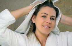 Jovem mulher que limpa o cabelo molhado com uma toalha fotos de stock