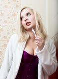 Jovem mulher que limpa seus dentes que sentam-se no toalete em um banheiro imagens de stock