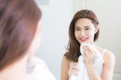 Jovem mulher que limpa sua cara com a toalha no banheiro Imagem de Stock