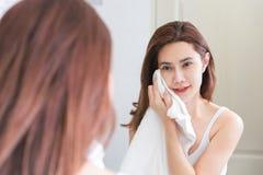 Jovem mulher que limpa sua cara com a toalha no banheiro Foto de Stock