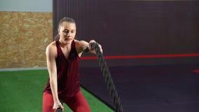 Jovem mulher que luta com cordas durante o exercício do cruz-treinamento no gym filme