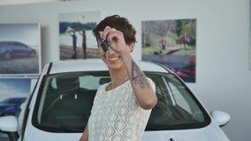 Jovem mulher que mantém chaves ao carro novo auto e que sorri na câmera filme