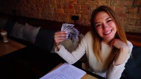 Jovem mulher que mantém contas nas mãos, trabalhando com papéis e mostrando os polegares acima no café vídeos de arquivo