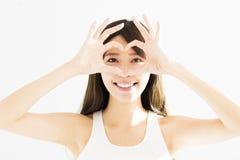 a jovem mulher que mantém o coração dado forma entrega perto dos olhos imagens de stock