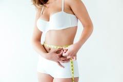 Jovem mulher que mede sua cintura pela medida da fita Imagem de Stock