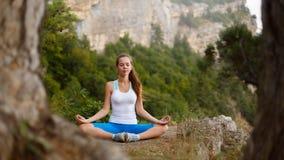 Jovem mulher que medita fora, menina que faz a elevação nas montanhas, conceito da ioga da autorreflexão do abrandamento foto de stock