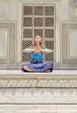 Jovem mulher que medita na parede de Taj Mahal Fotografia de Stock