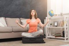 Jovem mulher que medita na pose dos lótus na mala de viagem imagem de stock