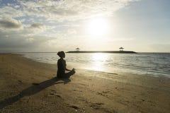Jovem mulher que medita na praia de Sanur Fotos de Stock
