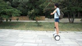 Jovem mulher que monta o mini 'trotinette' segway bonde da placa do pairo no parque verde filme