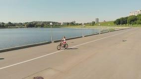 Jovem mulher que monta um ar livre da bicicleta no verão Terraplenagem do rio transporte Eco-amig?vel Tiro a?reo filme