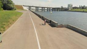 Jovem mulher que monta um ar livre da bicicleta no verão Terraplenagem do rio transporte Eco-amig?vel Tiro a?reo vídeos de arquivo