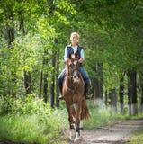 Jovem mulher que monta um cavalo fotografia de stock