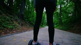 Jovem mulher que monta um giroscópio no parque Em torno das árvores Caminhada dos povos vídeos de arquivo